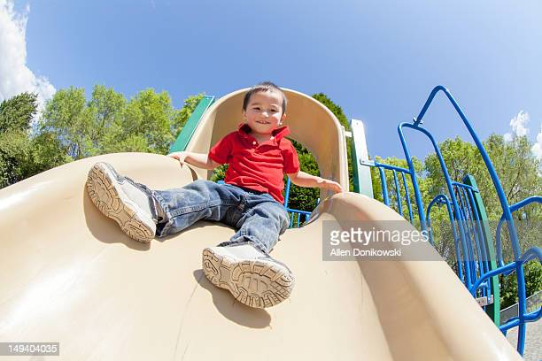Cute child on slide in sunshine