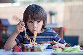 Cute child, preschool boy, eating spaghetti for lunch outdoors in garden, summertime