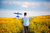 Cute child walking in the yellow field on a sunny summer day. Boy starts paper plane. Nature in the country. Back view