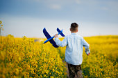 Cute child walking in the yellow field on a sunny summer day. Boy starts paper plane. Back view. Blur and soft focus.