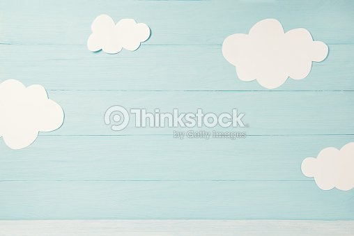 Cute children or baby card, white clouds on the light blue wooden background, tonned : Stock Photo