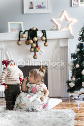 1a7ab1a52 Cute Christmas Baby Girl Playing With Santa Claus Toy Stock Photo ...