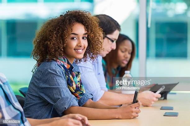 かわいい女の子中の大学生のメモクラスのスマートフォンを使用して