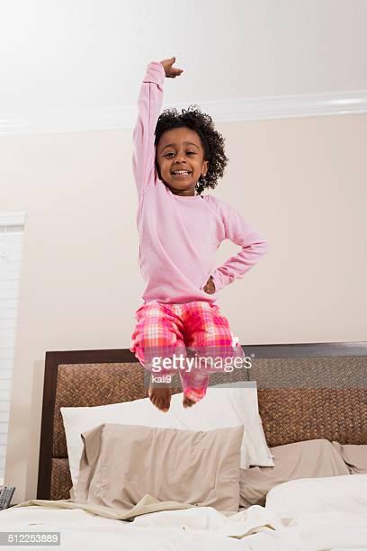 Sexy und selbstbewusst wirkenden kleinen afrikanischen amerikanischen Kinder auf und ab springen auf Bett