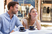 Cute couple facing relation difficulties on a cafe terrace