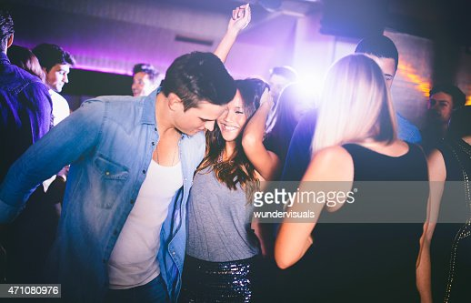 Cute couple flirting on dance floor in a night club
