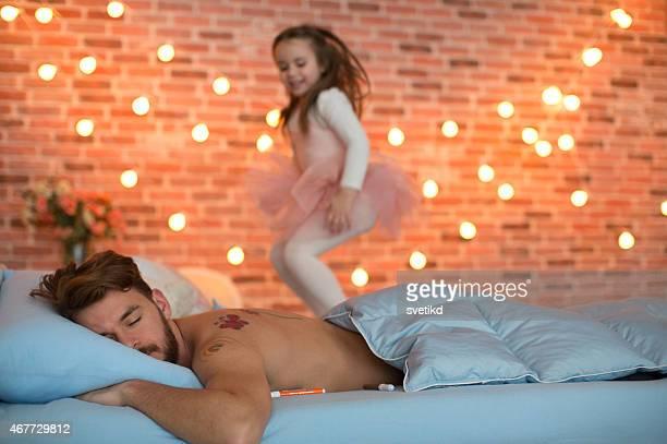 Jolie fille sautant sur un lit pendant que son père chambre séparés.