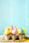 Cute and funny easter eggs with an egg decorated as a rabbit against a turquoise background, Vertical with copy space