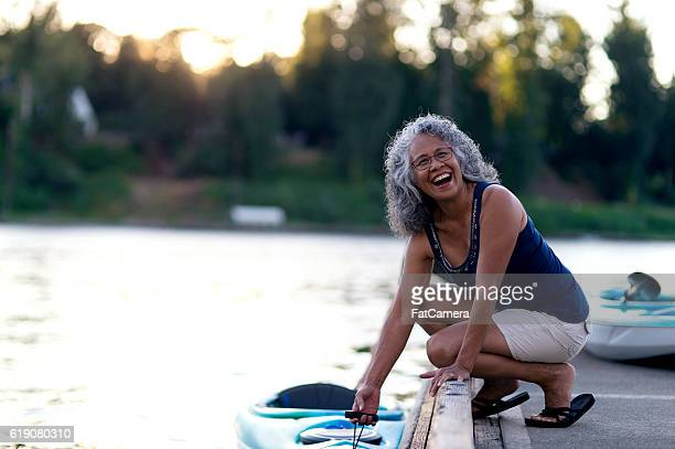 Cute elderly ethnic woman ready to kayak on the river