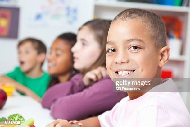 Cute elementary boy having lunch at school with classmates