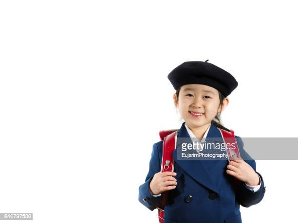 Cute elementary school girl in uniform, with red Japanese school bag