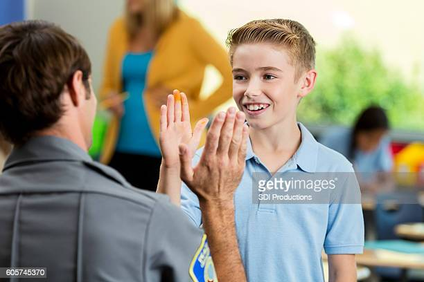 Cute elementary schoolboy gives high five to police officer