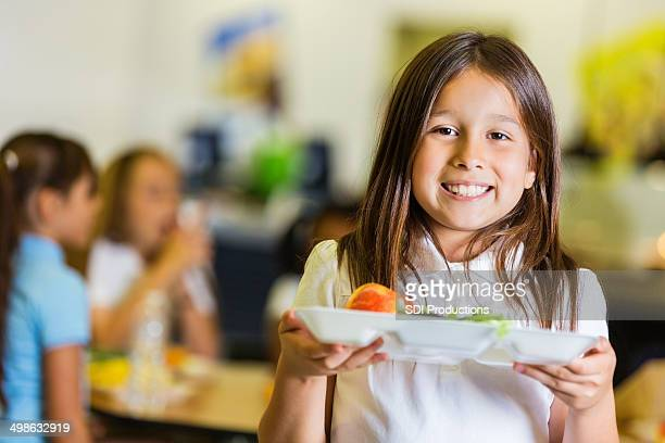 Cute elementary student holding lunch tray in school cafeteria