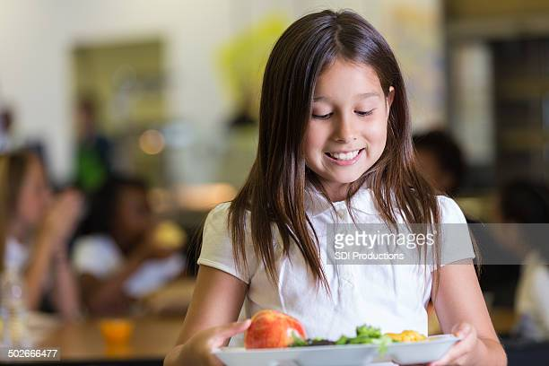 Cute elementary student looking at tray of cafeteria food