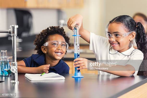 Cute elementary students smiling while doing science experiment in class