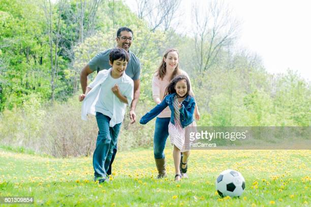 Cute Family Playing Soccer at the Park