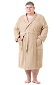 Cute fat man a mid adult age dressed in beige terry cloth bathrobe. The man is standing with hands in bathrobe pockets. He is smiling looking at the camera. Studio shooting on white background