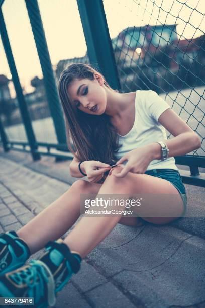 Süße Frau anlegen der Bandage auf blutige Knie Schmerzen