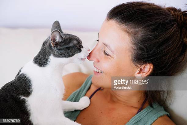 Cute femane cat licking her happy owner
