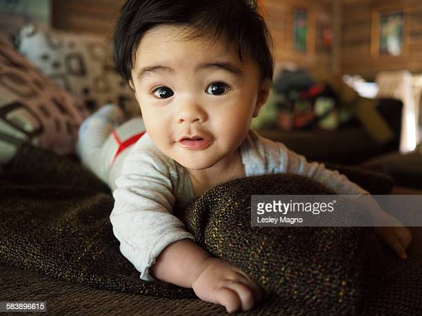 Cute five month old baby on sofa staring at camera