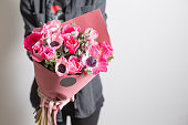cute flowers. beautiful bouquet of pink anemones in woman hand. the work of the florist at a flower shop.