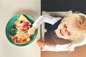 cute funny little girl eating pancakes with berries
