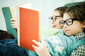 Cute geek boy and girl reading books.