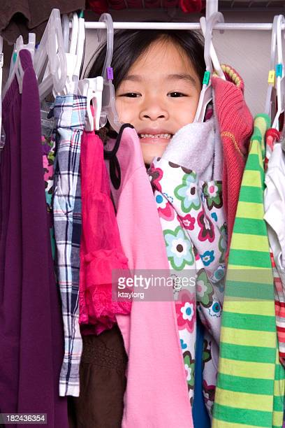 Cute girl behind clothes in closet