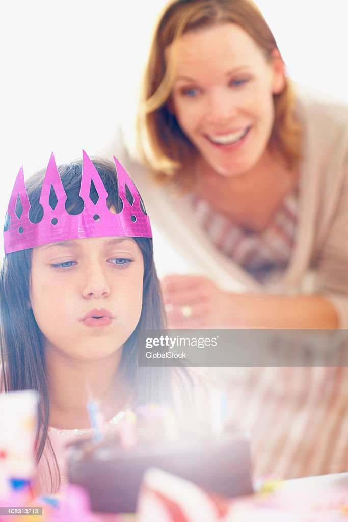 Cute girl blowing a the candles on her birthday cake : Stock Photo