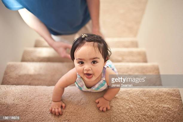 Cute girl climbing up carpeted staircase