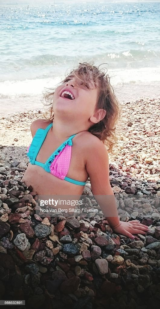 Cute Girl Covered With Stones At Beach