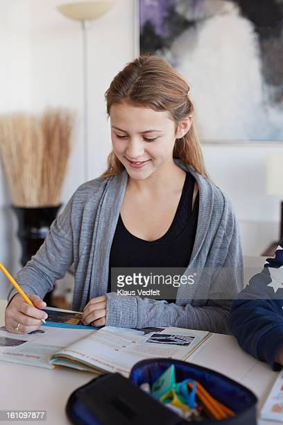 Cute girl doing homework writing in book