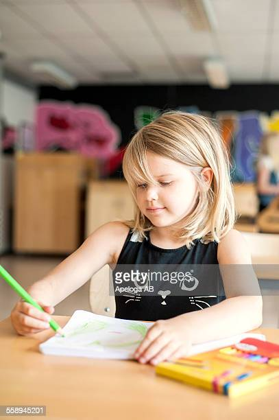 Cute girl drawing with color pencil in classroom