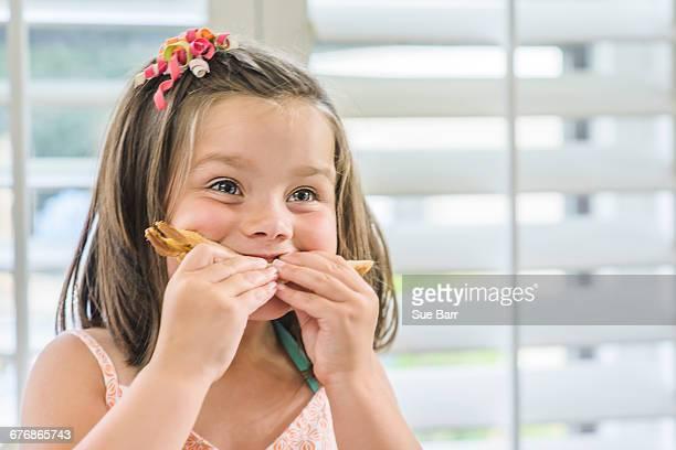 Cute girl eating sandwich in kitchen