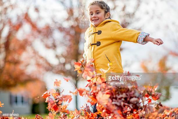 Jolie fille s'amuser dans les feuilles de