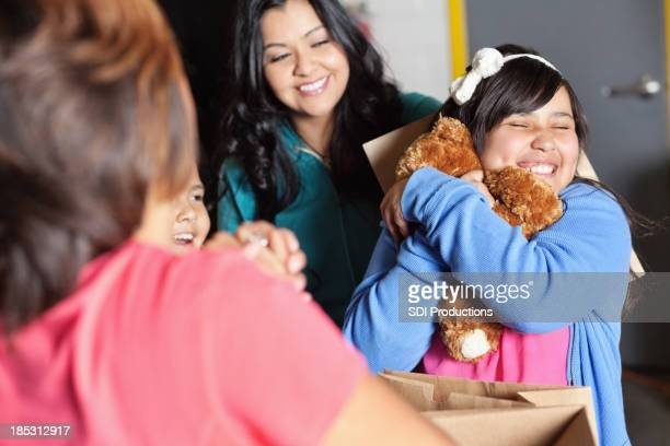 Cute girl holding a teddy bear that's been given