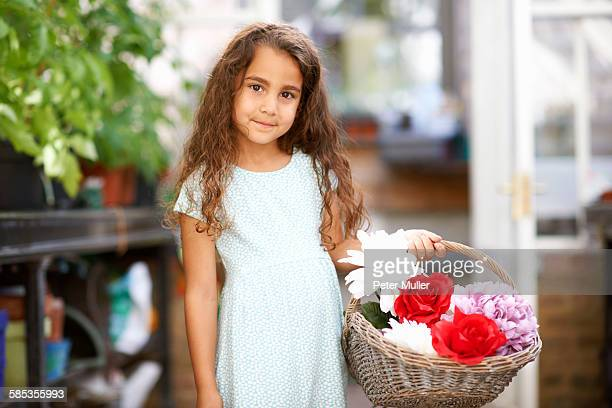 Cute girl holding basket of fresh flowers in greenhouse