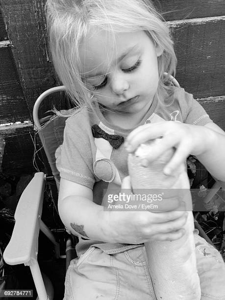 Cute Girl Holding Bread While Sitting On Chair In Yard