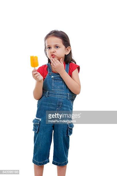 Cute girl holding flavored ice over white background