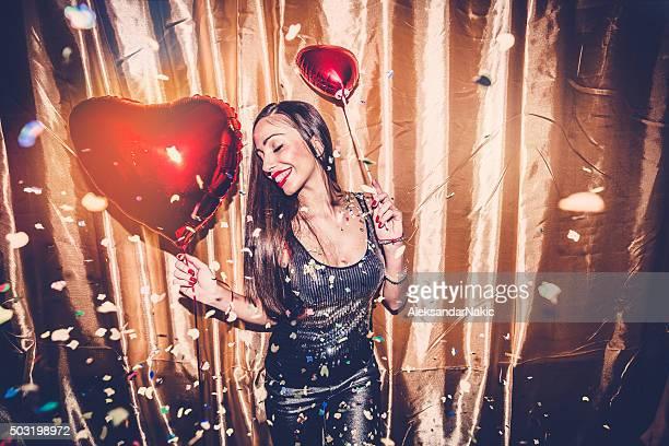 Cute girl holding red heart balloon