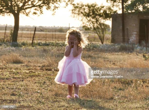 Cute Girl In Dress Covering Face With Hands While Standing On Grassy Field