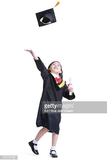 Cute girl in graduation gown throwing mortar board