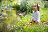 Sweet, happy little girl sitting on a grass in a park at a spring stream with flower in hand. Laughing, enjoying fresh air in forrest.