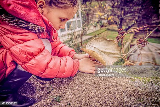 Cute Girl in Pink Coat  Playing with Sand, Winter, Europe
