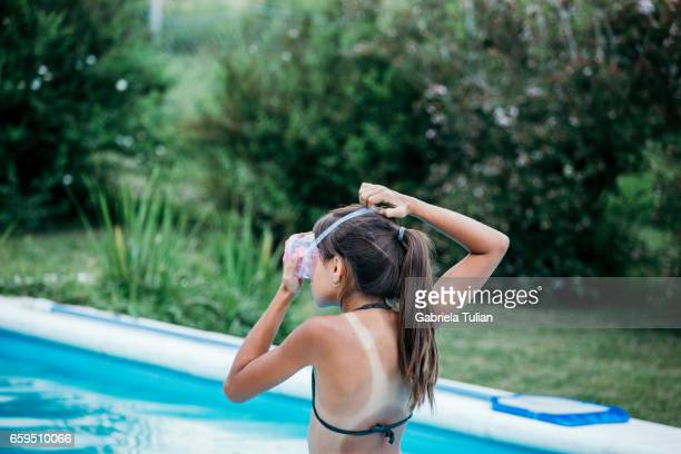 Cute girl in swimming pool putting her goggles