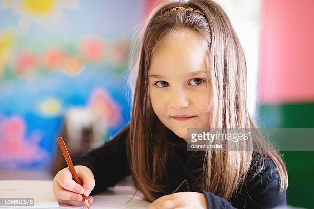 Cute girl in the classroom drawing