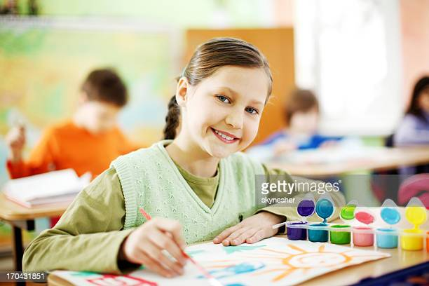 Cute girl is making pictures with watercolors.