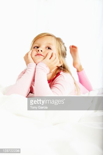 Cute girl laying in bed in pajamas. : Stock Photo