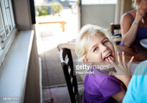 Cute girl licking food off her finger : Stock Photo