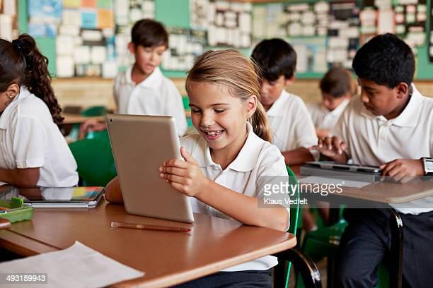 Cute girl looking at tablet in schoolclass